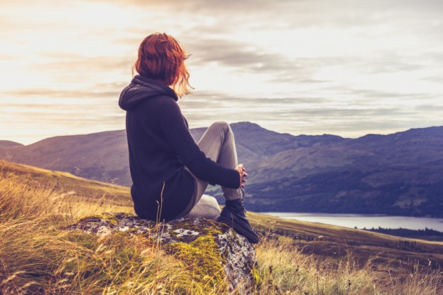 Woman admiring sunset from mountain top