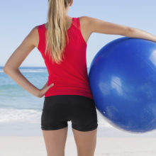 Fit blonde holding exercise ball looking at sea on the beach