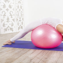 Woman does back stretch on stability ball