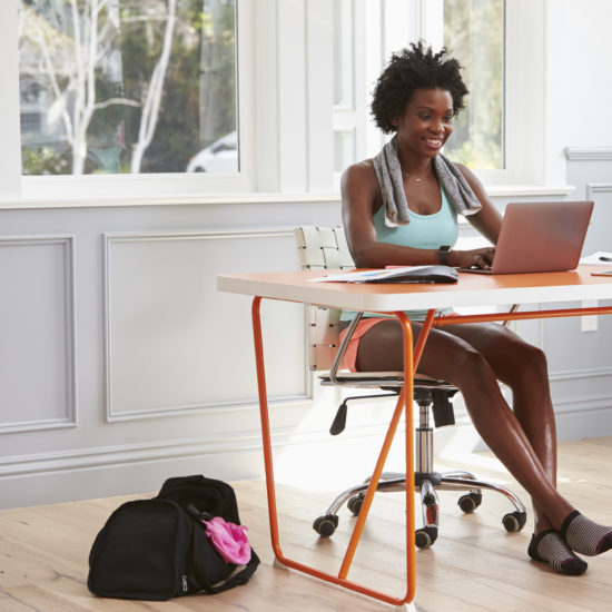 Young black woman using computer at home after exercising