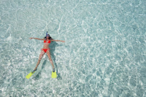 miami woman floating on crystal clear water