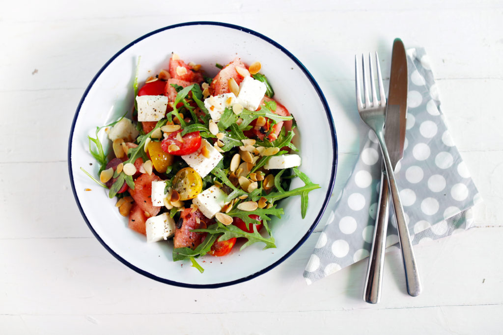 Watermelon and feta salad with cherry tomatoes and basil seeds.