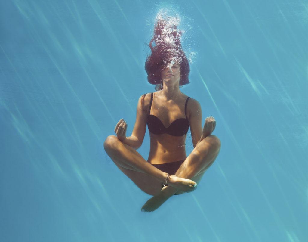 woman meditating under water