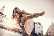 young happy couple piggybacking outdoors with their arms outstretched