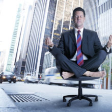 A  barefoot businessman, meditating in an office chair,  sits in the middle of a busy big city street.  The blurred buses and cars quickly move past him.  He is oblivious to their presence as he takes his time and filters out the big city hum.  The base of a row of large skyscrapers can be seen in the background