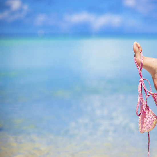 pink swimsuit on female leg on white tropical beach