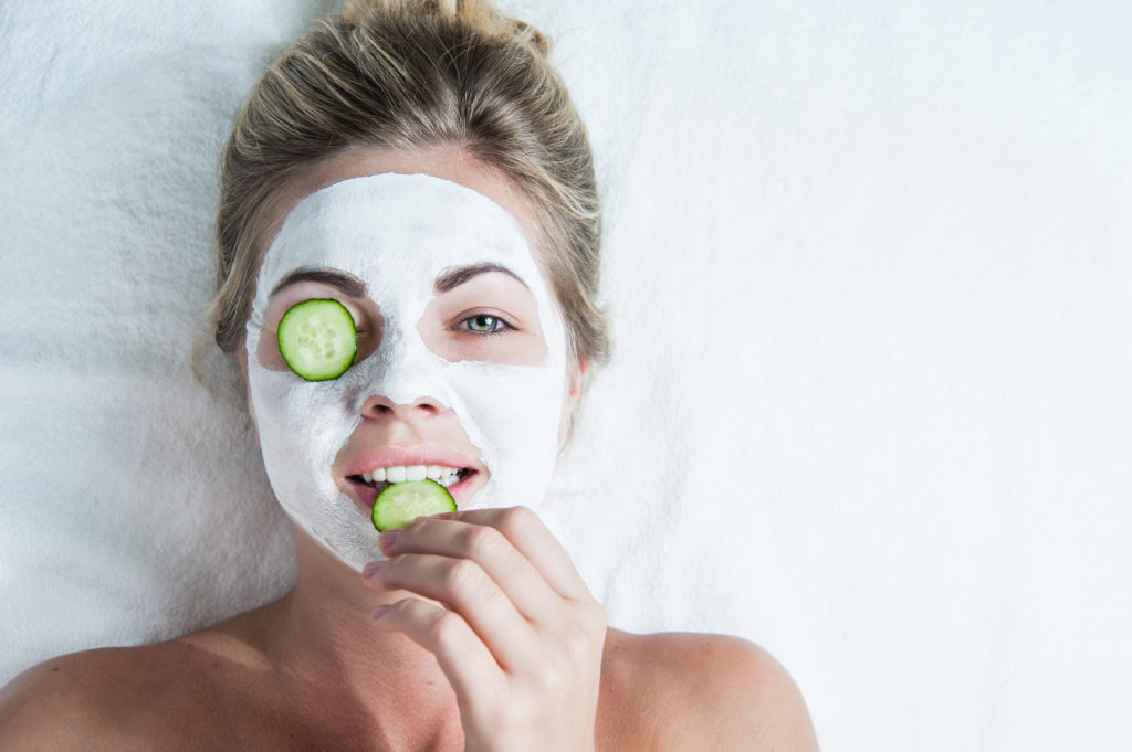 young woman with facial mask, biting on a cucumber