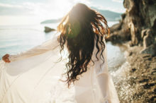 wind in hair dreamy girl with sunflare on beach 2