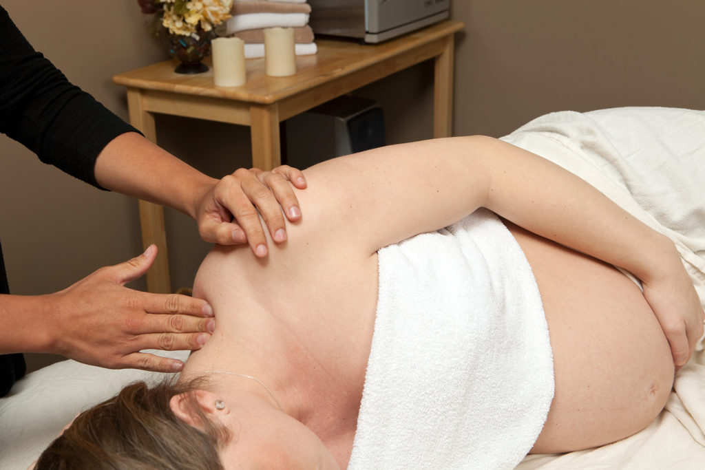 A pregnant woman is receiving a prenatal massage from a female massage therapist. This type of massage is used to relieve tension, stress and discomfort during pregnancy.