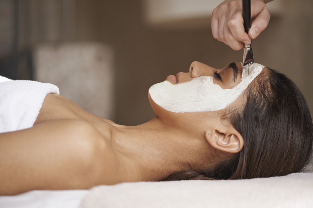A face mask being applied to a beautiful young woman at a beauty spa