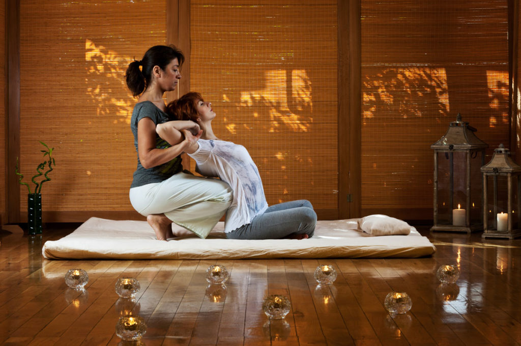 woman receiving thai massage surrounded by candles