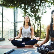two women performing kundalini yoga