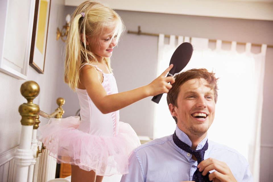 daughter brushing her father's hair before work