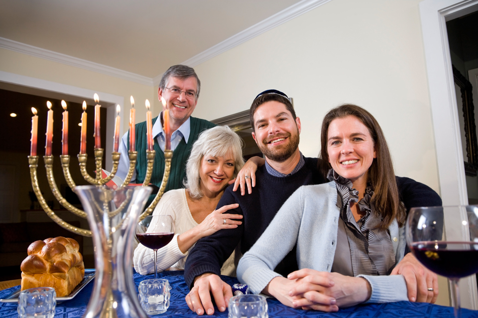 a family gathered for hanukkah with a menorah on the table